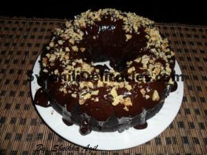 Chocolate cake with chocolate ganache and chopped walnuts.